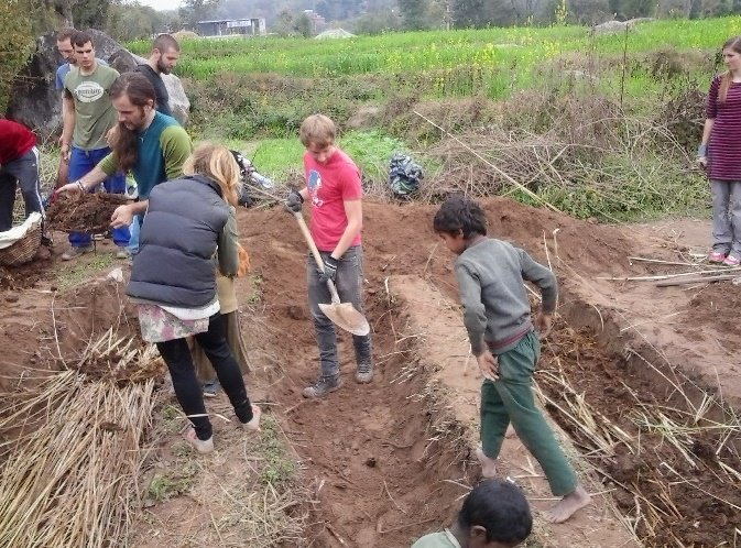 International volunteers for NGO Volunteer and interns participating in building raised soil beds for vegetable farming